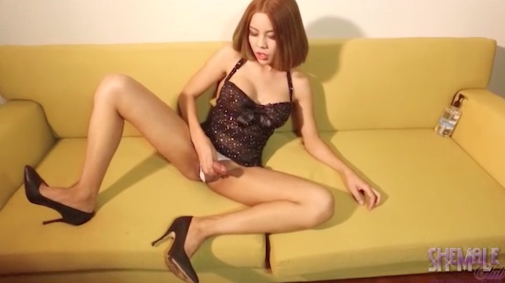 Nadia strokes her juicy cock over the couch.